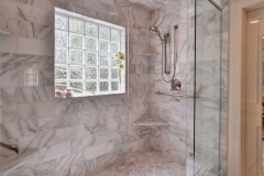 Calcutta Gold Marble, Diana Honed Marble, Window in Shower, Custom Cabinets and Mirror Surround